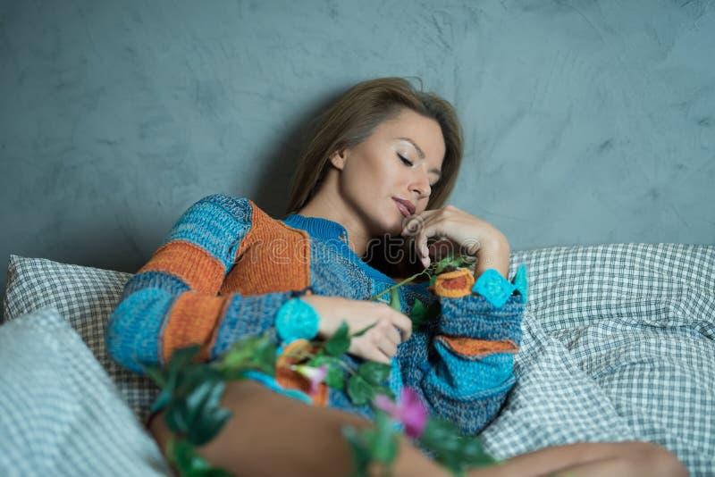 Eine Frau, die auf einem Bett liegt und einen Pullover trägt stockfotografie