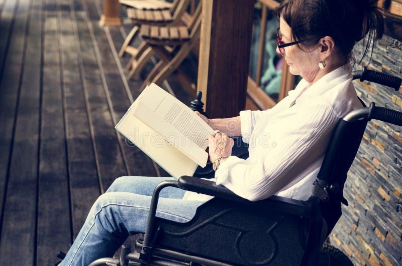 Eine Frau, die auf einem Rollstuhl und einem Ablesen sitzt stockfoto