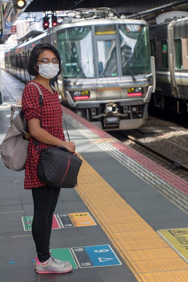 Eine Frau, die auf einen Zug wartet, stockfotos