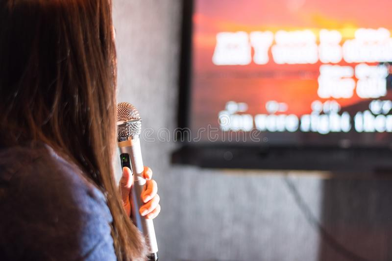 Eine Frau, die an der Karaokestange hält ein Mikrofon vor Fernsehschirm mit Lyriken singt stockfoto