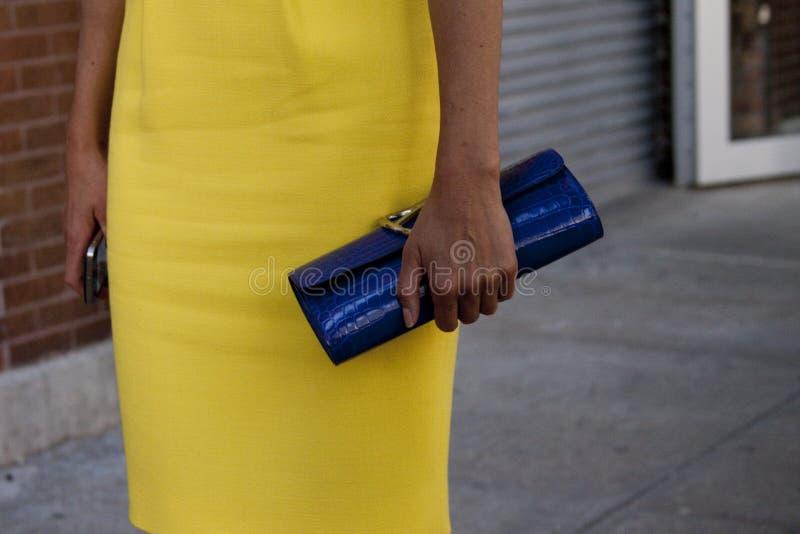 Eine Frau, die draußen ihren Kupplungsgeldbeutel hält stockfotos