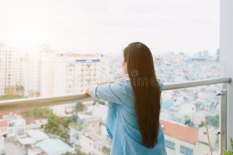 Eine Frau, die draußen von ihrem Haus denkt und schaut lizenzfreie stockbilder