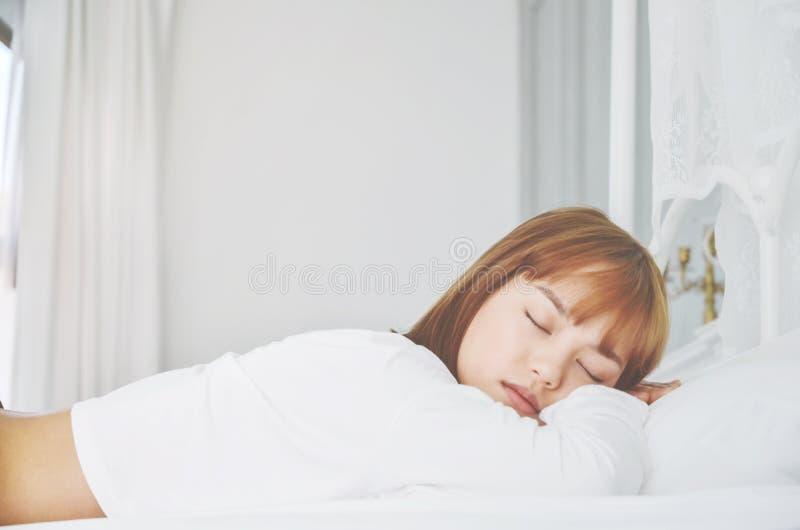 Eine Frau, die ein weißes Kleid trägt, schläft sie stockfotografie