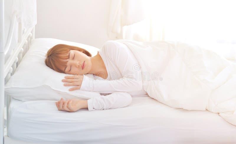 Eine Frau, die ein weißes Kleid trägt, schläft sie stockbilder