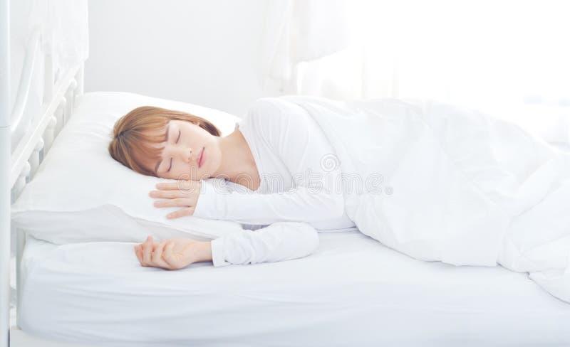 Eine Frau, die ein weißes Kleid trägt, schläft sie lizenzfreie stockfotos