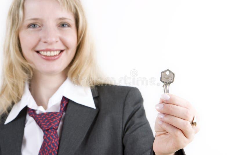 Eine Frau, die eine silberne Taste anhält lizenzfreie stockfotografie