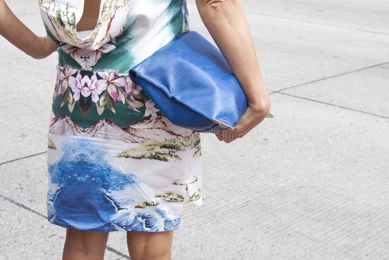 Eine Frau, die einen Designerkupplungsgeldbeutel hält und hohe Absätze trägt stockfotografie