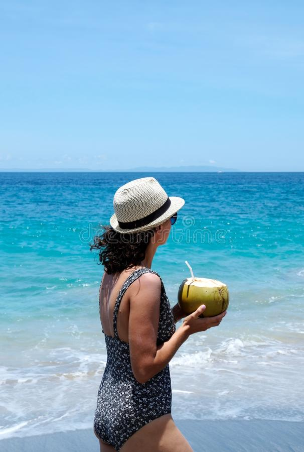 Eine Frau, die einen Hut und einen schwimmenden Anzug gehen entlang eine schöne Küstenlinie, Bali trägt stockfotografie