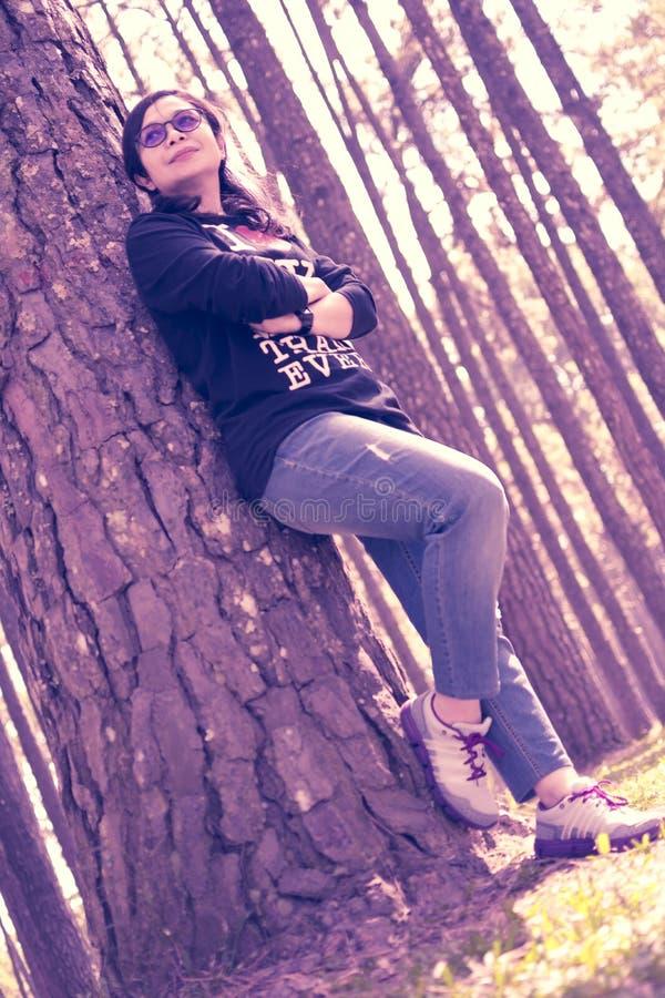 Eine Frau, die gegen einen Baum steht lizenzfreie stockfotografie