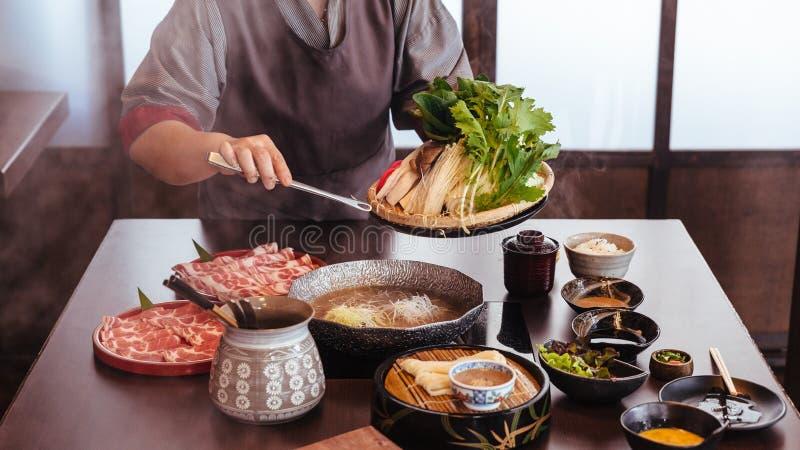 Eine Frau, die Gemüse in heißen Topf durch Zangen mit Rindfleisch Wagyu A5 und geschnittenes Kurobuta in Shabu-klarer Brühe mit S stockbild
