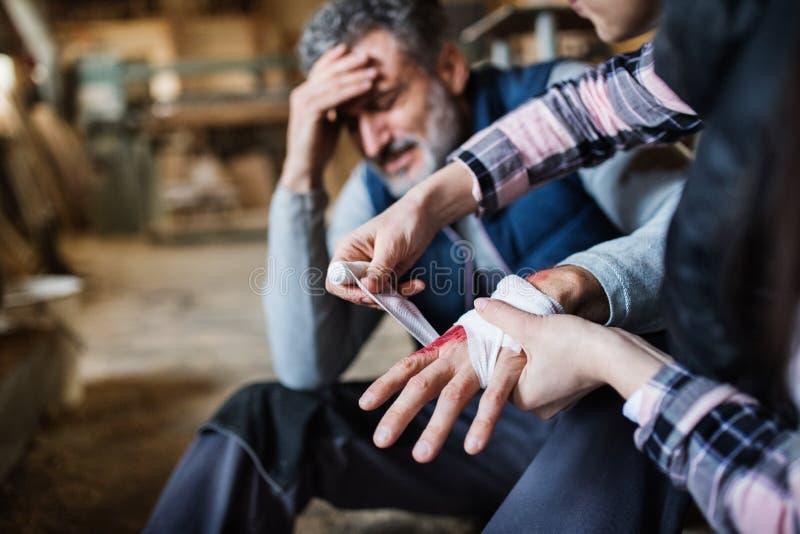 Eine Frau, die eine Hand einer Mannarbeitskraft nach Unfall in der Zimmereiwerkstatt verbindet stockfoto