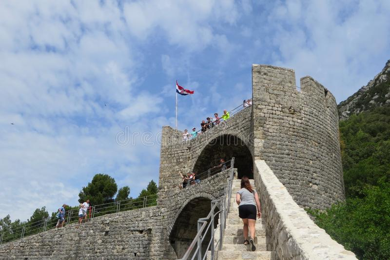 Eine Frau, die hoch oben auf den Wänden von Ston, in der alten Stadt von Ston, Kroatien klettert lizenzfreie stockbilder