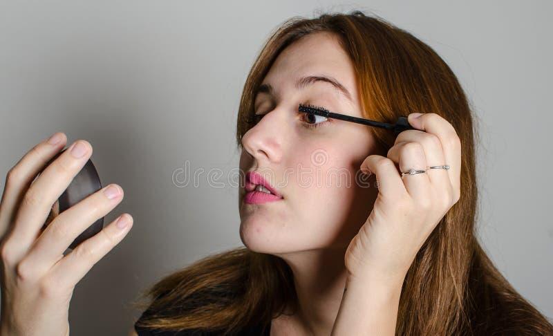 Eine Frau, die ihre Peitschen malt stockbilder