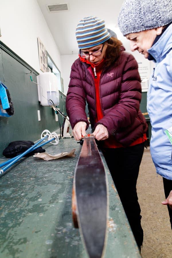 Eine Frau, die jemand zeigt, wie man Cross Country-Skis vorbereitet lizenzfreies stockbild