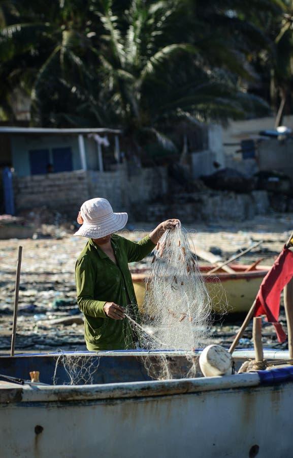 Eine Frau, die mit den Netzen in Phan Thiet, Vietnam arbeitet lizenzfreie stockbilder