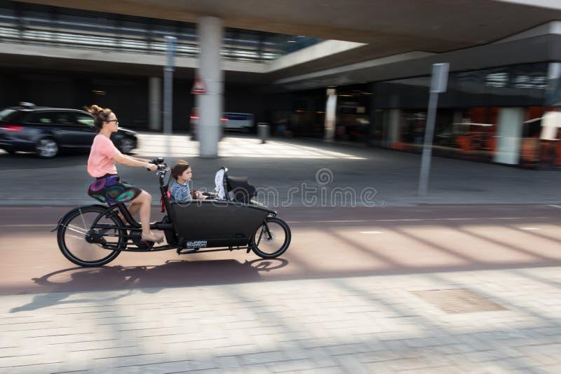 Eine Frau, die mit Kindern auf einem Frachtfahrrad am zentralen Bahnhof Amsterdams, die Niederlande radfährt lizenzfreie stockbilder