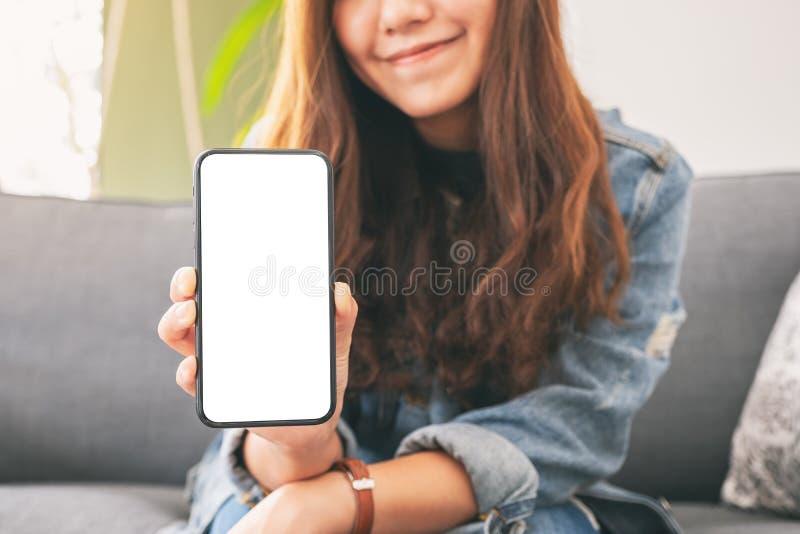 Eine Frau, die schwarzen Handy mit leerem Bildschirm im Café hält und zeigt lizenzfreie stockfotos