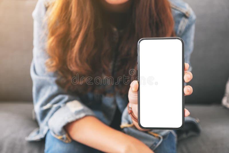 Eine Frau, die schwarzen Handy mit leerem Bildschirm im Café hält und zeigt stockfotografie