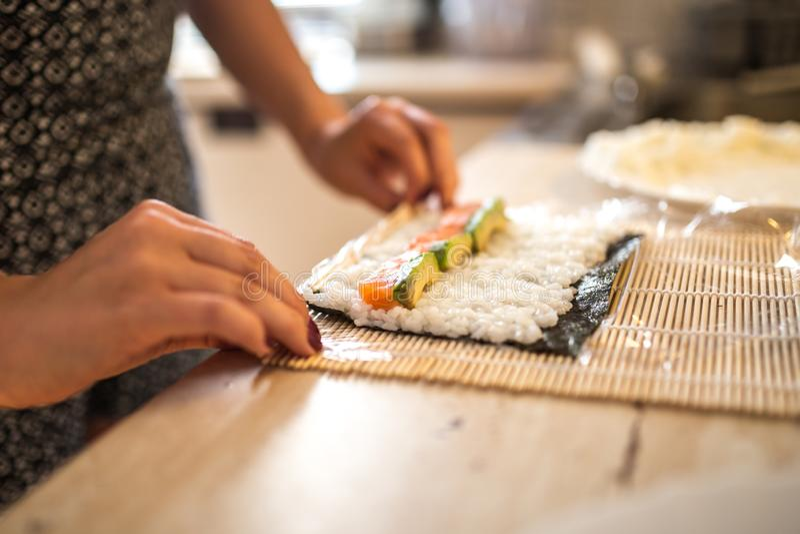 Eine Frau, die selbst gemachte Sushi und Rollen vorbereitet Formung von Sushi Die Schritte für das Herstellen von Sushi Ansicht d stockfotografie