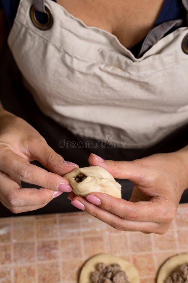Eine Frau, die Torten mit Fleisch macht lizenzfreie stockbilder