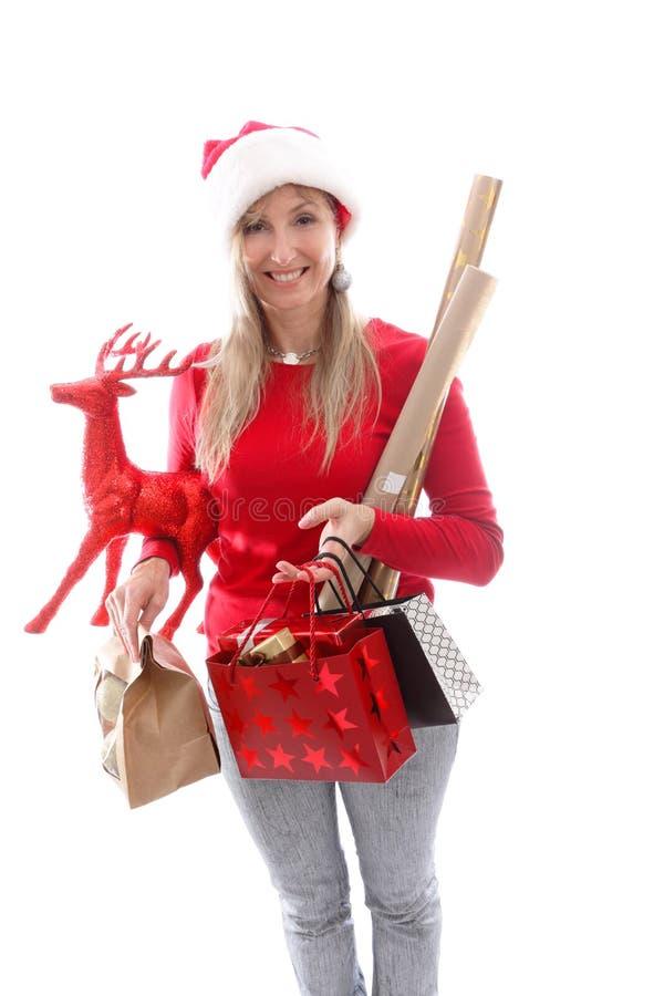 Eine Frau, die verschiedene Geschenke und Dekorationen für Weihnachten trägt lizenzfreies stockbild