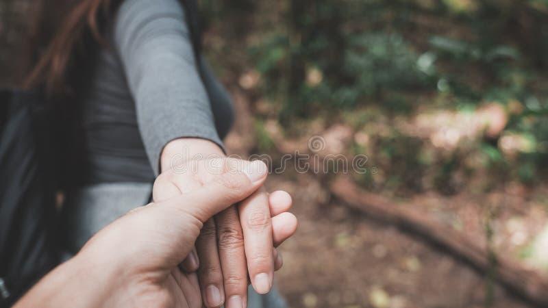 Eine Frau, die vorwärts geht und ihre Freund ` s Hand während Trekking hält stockbild