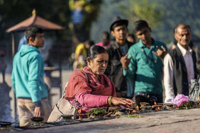 Eine Frau, die Weihrauch einem Tempel in Nepal anbietet lizenzfreie stockfotografie