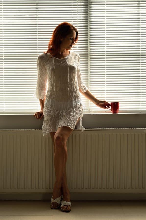 Eine Frau, die zu Hause stillsteht lizenzfreie stockbilder
