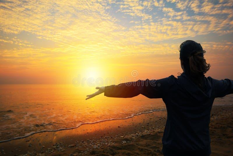 Eine Frau, die zum Sonnenuntergang auf dem Strand schaut stockbilder