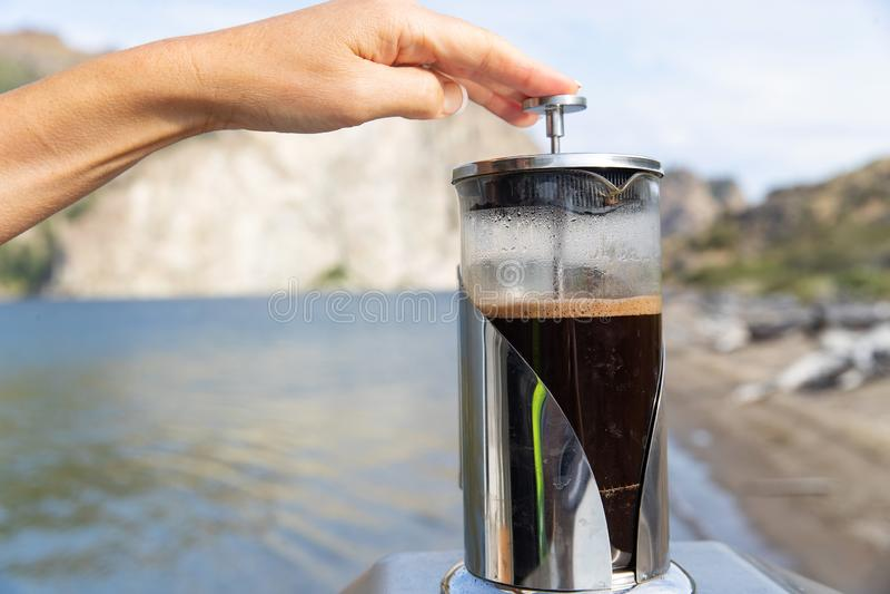 Eine Frau drückt den Kolben nieder, um einen heißen Tasse Kaffee mit einer französischen Presse während Außenseite auf einem Sees lizenzfreie stockbilder