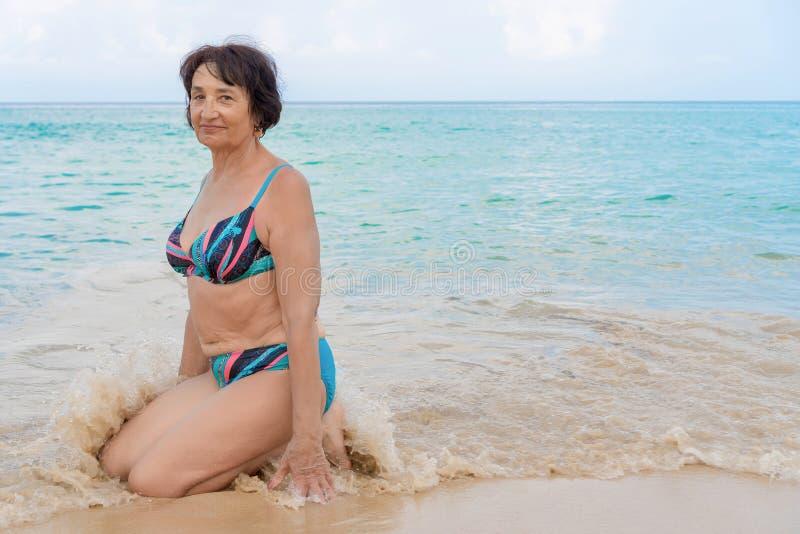 Eine Frau in einem Badeanzug, der die Kamera und und das Lächeln betrachtet stockfotos