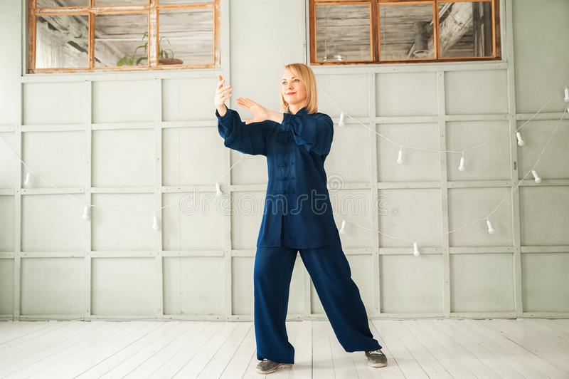 Eine Frau in einem blauen Kimono nimmt an chinesischer Kampfkunst Tai Chi-Nahaufnahme und Kopienraum teil stockbilder