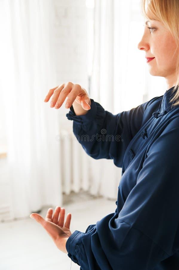 Eine Frau in einem blauen Kimono nimmt an chinesischer Kampfkunst Tai Chi-Nahaufnahme und Kopienraum teil stockfotografie