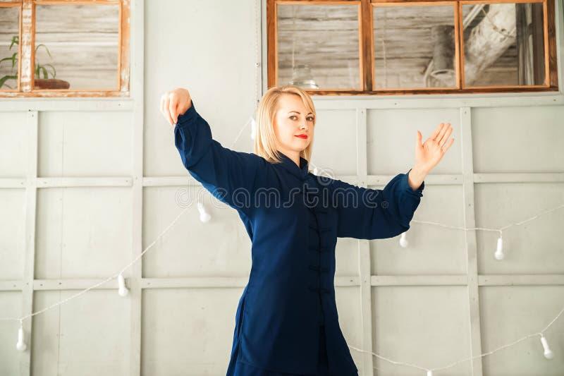 Eine Frau in einem blauen Kimono nimmt an chinesischer Kampfkunst Tai Chi-Nahaufnahme und Kopienraum teil lizenzfreies stockfoto
