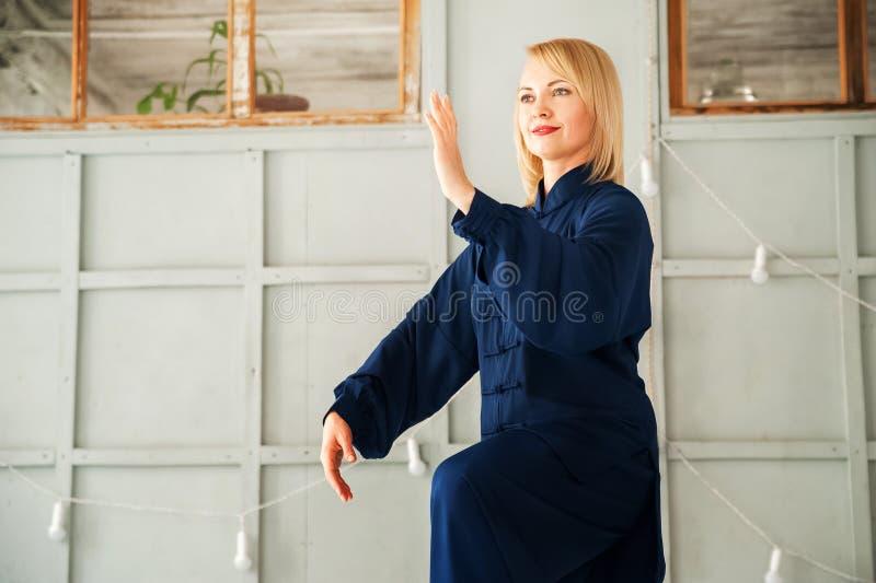 Eine Frau in einem blauen Kimono nimmt an chinesischer Kampfkunst Tai Chi-Nahaufnahme und Kopienraum teil stockbild