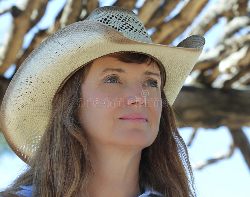 Eine Frau in einem Cowboyhut unter einem Ramada lizenzfreie stockbilder
