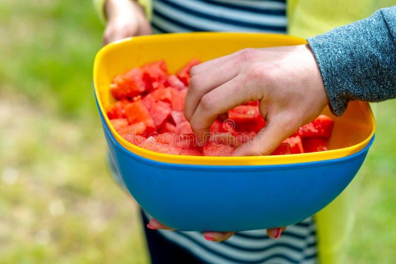 Eine Frau an einem heißen Tag bietet geschnittene Stücke der Wassermelone an lizenzfreie stockbilder