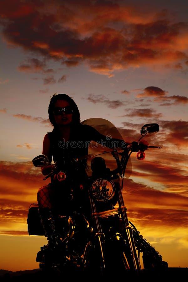 Eine Frau in einem Motorrad im Sonnenuntergangsitzen stockfotografie