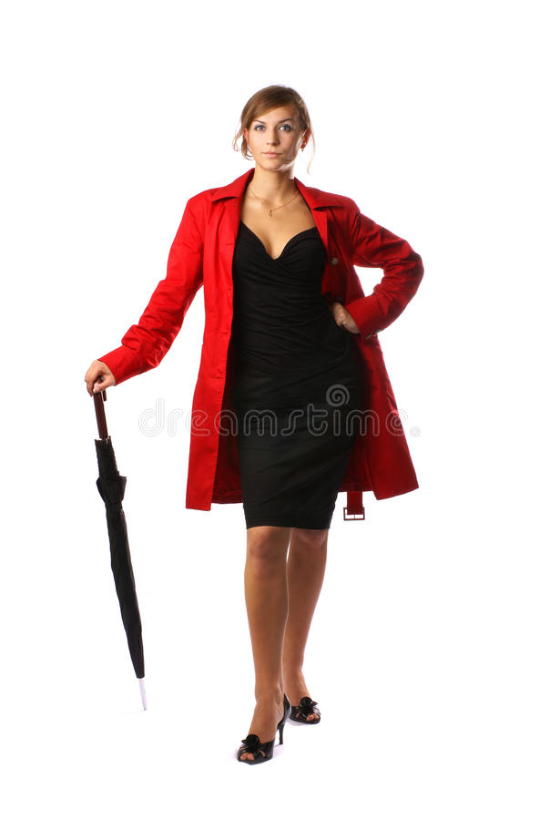 Eine Frau in einem roten Mantel und in einer Holding ein Regenschirm stockfoto