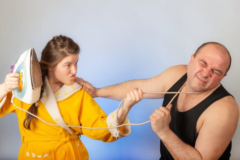 Eine Frau in einer gelben Robe schlägt einen kahlen Ehemann, das Konzept eines Familienstreites stockbild