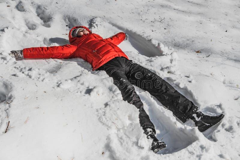 Eine Frau in einer roten Jacke und schwarze Hosen in einem weißen Schnee in einem Winterpark Eine Frau liegt im Schnee wie Engel lizenzfreies stockbild