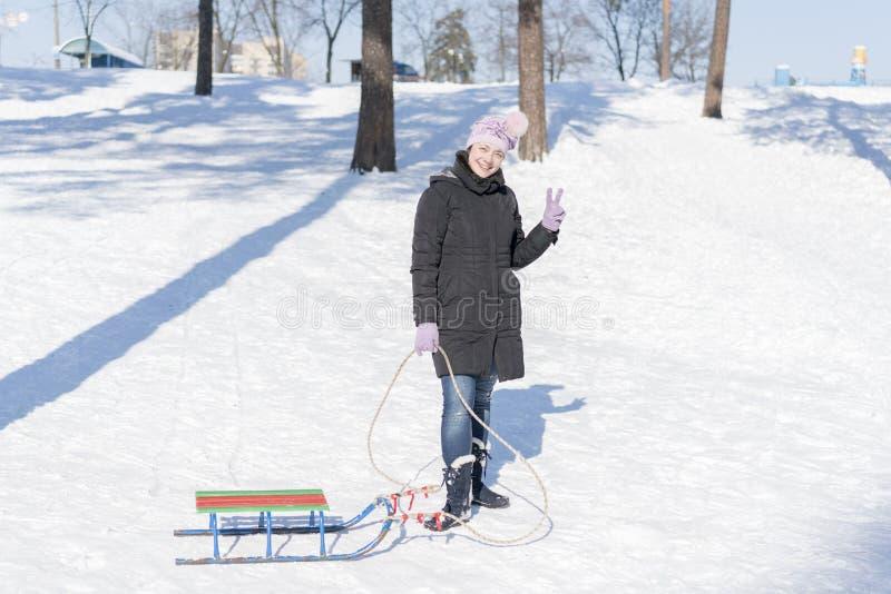 Eine Frau in einer schwarzen Winterjacke mit Schlitten in einem schneebedeckten Park oder in einem Wald stockbild