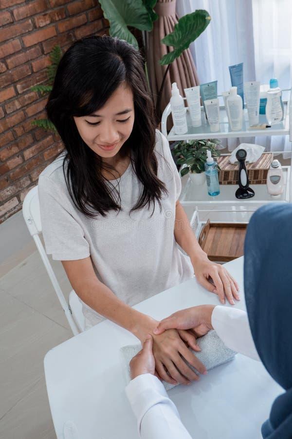 Eine Frau erhält einen Komfort der Handlotion sehr mit Kosmetiker lizenzfreie stockbilder