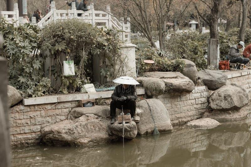 Eine Frau fischt in Lotus Pond Lake stockbilder