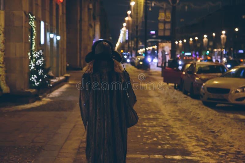 Eine Frau geht hinunter die Straße nachts stockfotos