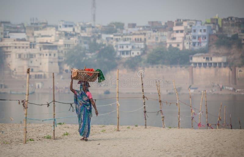 Eine Frau geht mit Wäschekorb auf ihrem Kopf stockfotos