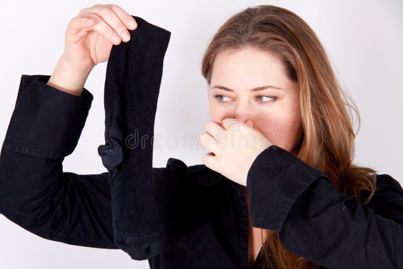 Eine Frau hält eine smelly Socke an stockfoto
