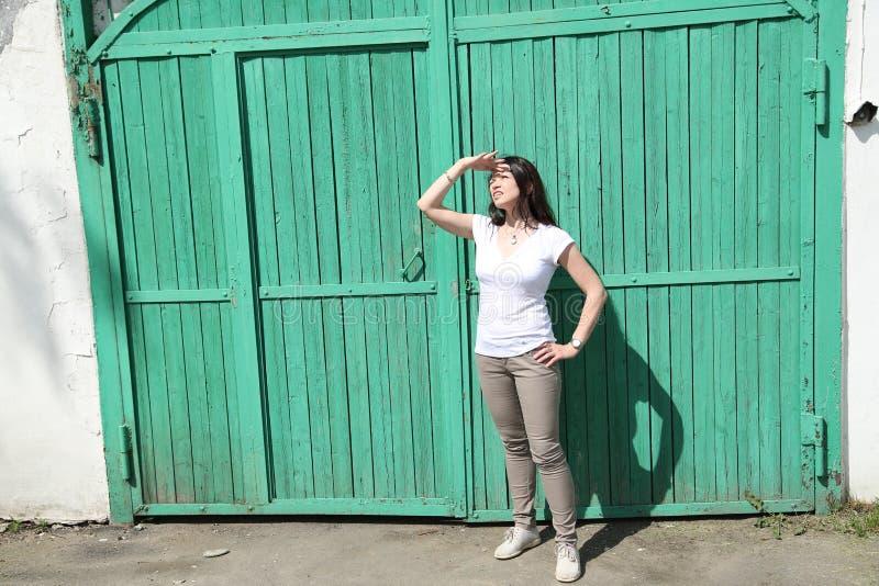 Eine Frau hält ihre Palme gegen ihre Stirn und betrachtet oben dem Himmel lizenzfreie stockbilder