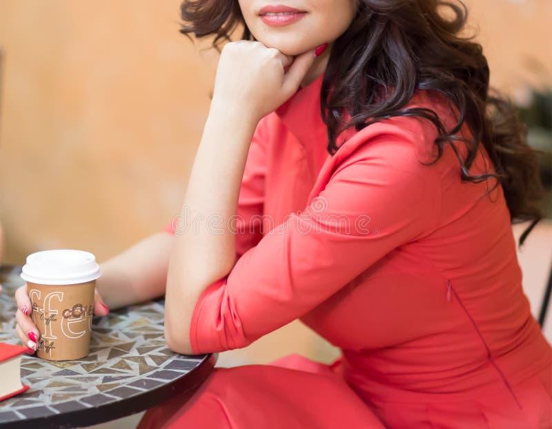 Eine Frau hält eine Pappe Glas mit dem Kaffee und sitzt an einem Tisch in einem gemütlichen Café stockfoto