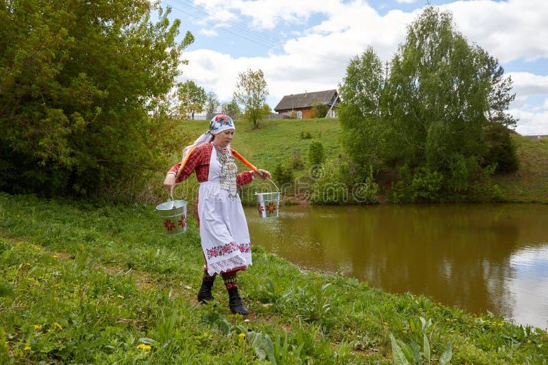 Eine Frau im Dorf nimmt an Haushaltung teil Das Mädchen trägt Eimer Wasser von einer sauberen Quelle stockbild